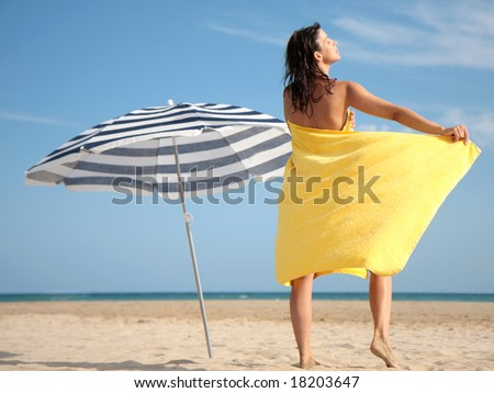 Woman with towel on the beach while sunbathing - stock photo