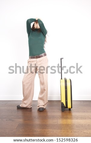 woman with trousers detail holding a yellow trolley - stock photo