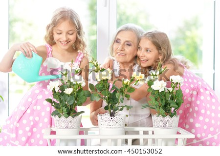 woman with tweenie   girls watering flowers - stock photo