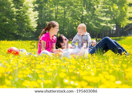 Woman with two cute kids on the park in spring, selective focus - stock photo