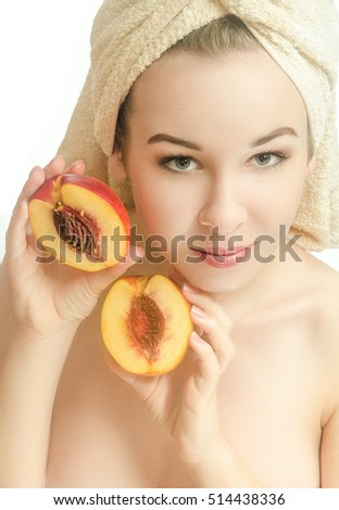 Woman with two halves of a peach and a towel on his head. Beauty.