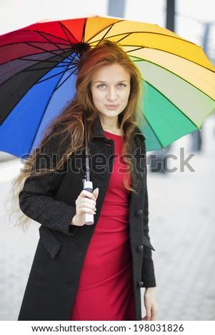 Woman with umbrella at hand posing at camera - stock photo