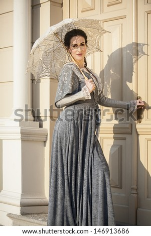 woman with umbrella in addition to columns - stock photo