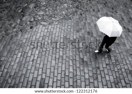Woman with umbrella in the rain on paving stone road - stock photo