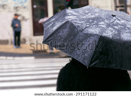 Woman with umbrella on rainy day waiting to cross the street