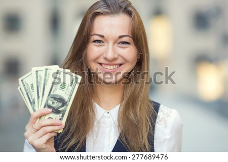 Woman with us dollar money. Business woman holding money. Woman and money. Young business woman holding a lot of USA hundred dollar bills. Business woman has earned a good amount of dollars. - stock photo