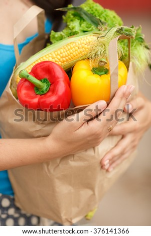 Woman with vegetables in shopping bag at street market, girl with organic food near supermarket, woman with bag of food at street market, selective focus, soft grain filter, series
