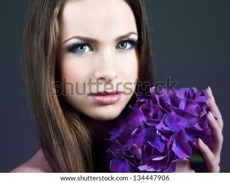 Woman with violet flowers. Fashion photo.