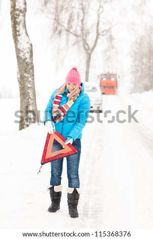 Woman with warning triangle car snow breakdown problem winter traffic - stock photo