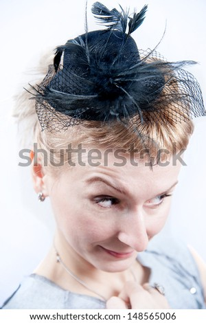 Woman with weird expression wearing a 30s hat - stock photo