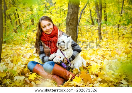woman with west highland terrier in the park