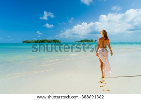 Woman with white clothe walking  on the beach - stock photo