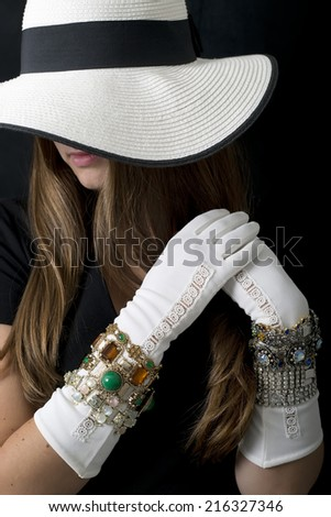 Woman with white floppy hat with black ribbon, white gloves and lots of bling or bracelets, with only lips showing. - stock photo
