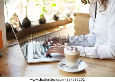 woman with white shirt typing on keyboard pc laptop and cappuccino coffee cup ready thinking on light brown wooden table - stock photo
