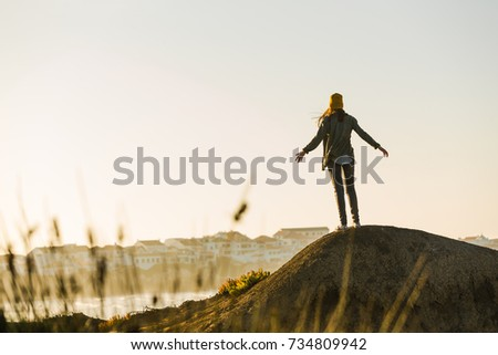 Woman with yellow cap over the cliff seeing the beach