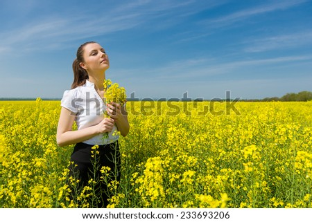 woman with yellow flowers on the field - stock photo