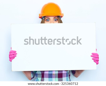 Woman worker builder hiding face behind white sign board. Building helmet. Pink glow. - stock photo