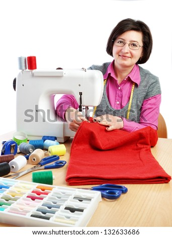 Woman worker sews on the sewing machine. - stock photo