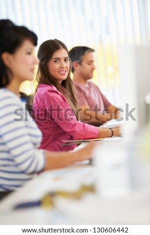 Woman Working At Desk In Busy Creative Office - stock photo