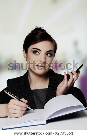 woman working at her desk on her phone holding a compact mirror - stock photo