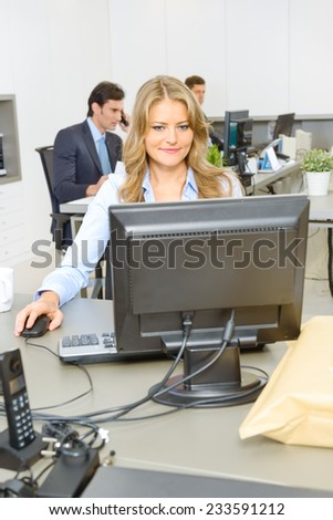 Woman working at her desk, with people working at the background  - stock photo