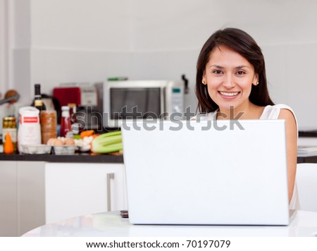 Woman working at home on a laptop computer - stock photo
