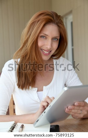 Woman working at home with electronic tablet - stock photo