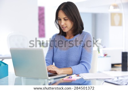 Woman Working At Laptop In Home Office - stock photo