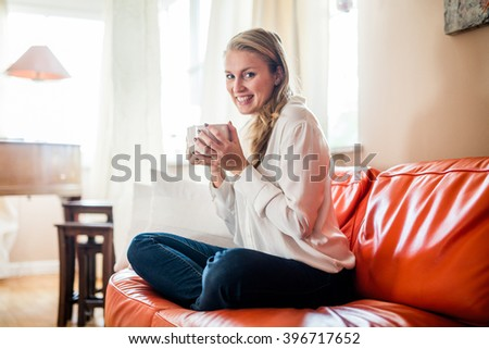 Woman working from home on her relaxing orange couch - stock photo