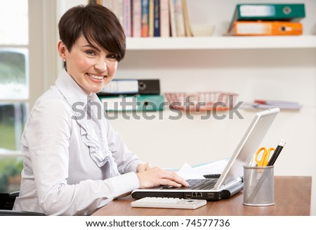 Woman Working From Home Using Laptop - stock photo