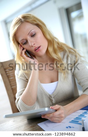 Woman working from home with smartphone and tablet - stock photo