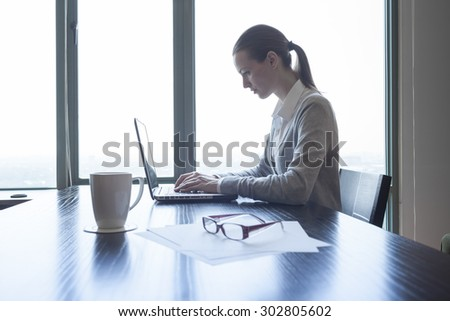 Woman working hard in her office.  - stock photo