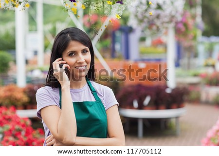 Woman working in garen center making a call and Smiling - stock photo