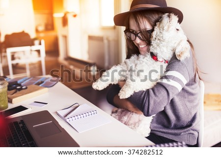 Woman working in her office and hugging her puppy - stock photo