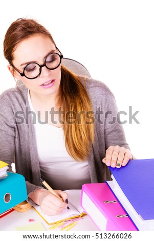 Woman working in office. Businesswoman or secretary with many documents folders bills on her desk working. College, workplace education concept.