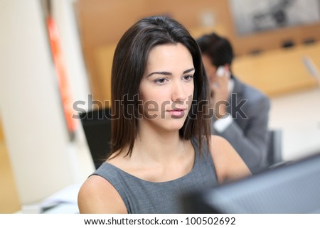Woman working in office in front of desktop computer - stock photo