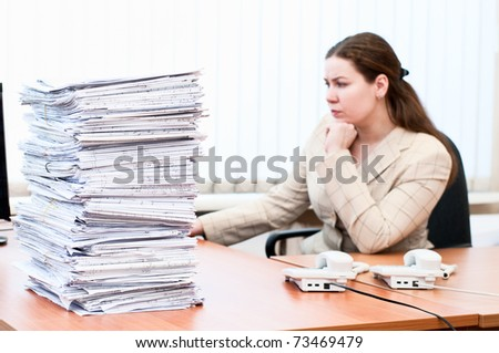 Woman working in office room. Focus on pile of blueprints - stock photo