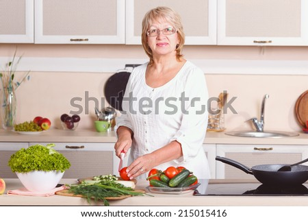 Woman working in the kitchen. Mom while she work something else. Mother prepares a salad. Cooking. Woman while preparing food in kitchen. Beautiful adult multiracial woman while making salad. Retro. - stock photo