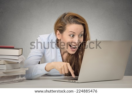 Woman working on computer ready press enter button isolated grey office wall background. Funny funky crazy looking girl excited what she see on laptop screen browsing internet. Face expression emotion - stock photo