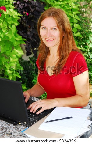 Woman working on her computer at home, small business owner - stock photo