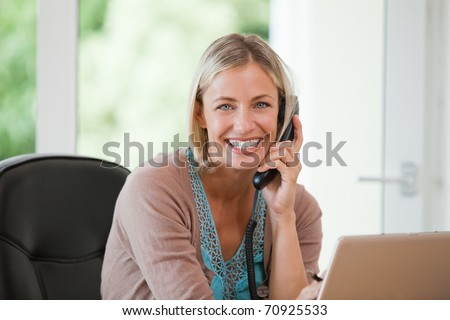 Woman working on her computer while she is phoning at home - stock photo