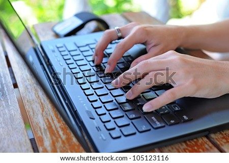 Woman working on her laptop on a terrace - stock photo