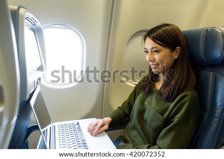 Woman working on laptop computer inside airplane