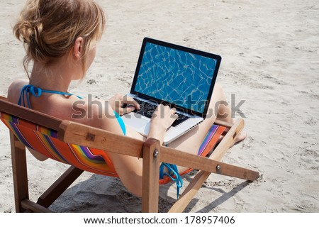 woman working on laptop on the beach - stock photo