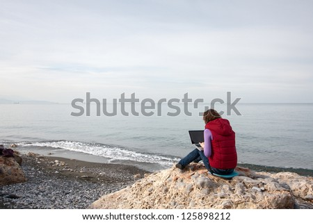 Woman working on the laptop, sitting at the sea coast - stock photo