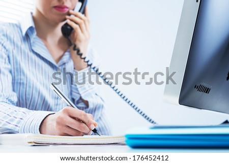 Woman working on the phone and writing down notes at office. - stock photo