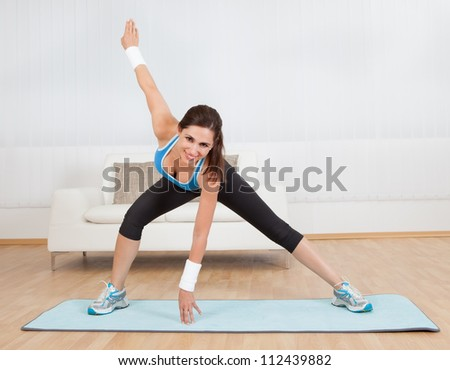 Woman working out on a mat at a gym doing stretch exercises - stock photo