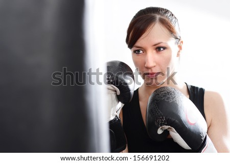 Woman working out on punch bag in gym - stock photo