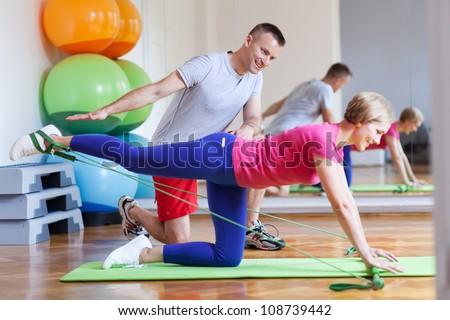 Woman working out while instructor assisting her - stock photo