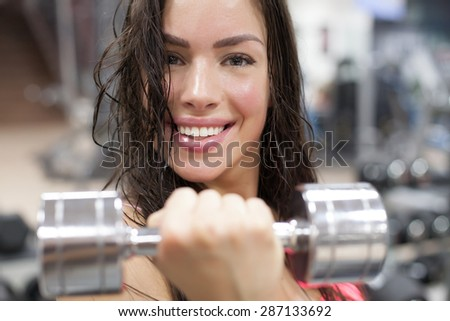 Woman working out with chrome weights - stock photo